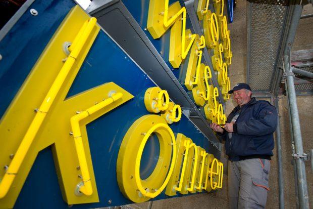Timo Wernicke bei den letzten Handgriffen. Ab Donnerstag strahlt die historische Leuchtreklame ohne Baugerüst. Foto: Norman Rembarz/Westend-PR