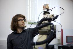 Florian Müller, Projektmitarbeiter der Fakultät Elektrotechnik und Informationstechnik der HTWK Leipzig, dirigiert den handgeführten Roboter, der auf der Fachmesse INTEC zu sehen sein wird. Quelle: Kristina Denhof
