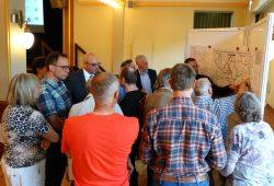 Eine der vier Gruppen, die an den Info-Wänden mit den ausgehängten Plänen mit den Verkehrsplanern des MDV ins Gespräch kommen. Foto: Patrick Kulow.