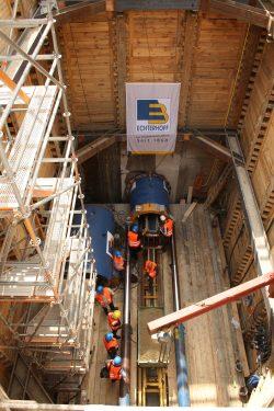 Blick in den Schacht mit dem Ende der Vortriebsmascine (oben) und dem starken Hydrailikgestänge, das die Stahlrohre in die Tunnelbohrung schieben wird. Foto: Ralf Julke