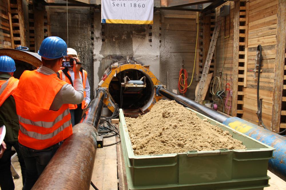 Blick über die Lore mit dem ausgefrästen Bodenmaterial in die Röhre der Vortriebsmaschine mit dem Förderband. Foto: Ralf Julke