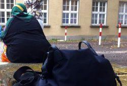 """Eine Frau hat erschöpft vor der Ernst-Grube Halle Platz genommen. HIer """"wohnen"""" derzeit rund 400 Flüchtlinge noch bis März 2016 in Leipzig. Foto: L-IZ.de"""