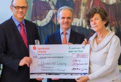 Alexander Prinz von Sachsen (Mitte) übergibt einen Spendenscheck an Rektorin Prof. Dr. Beate Schücking und Prof. Dr. Dietger Niederwieser. Foto: Uni Leipzig