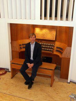 Daniel Beilschmidt an seiner noch unvollendeten Jehmlich-Orgel, die Verkleidung des Spieltisch ist mit Kirschbaumholz gefasst. Foto: Karsten Pietsch