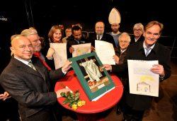 Leipzigs Oberbürgermeister Burkhard Jung (r.) nimmt von Vertretern der Kirche erste handgeschriebene Bibelseiten entgegen. Foto: Dieter Grundmann/Westend-PR