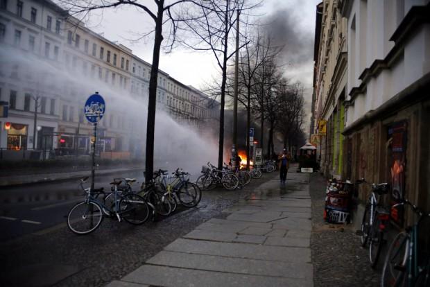 Die Polizei löscht eine Barrikade mittels Wasserwerfer