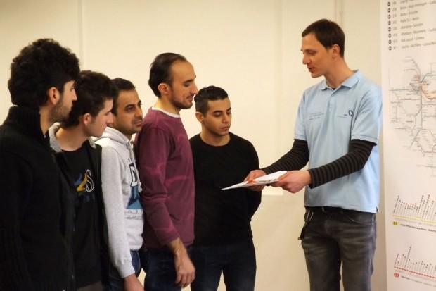 MDV-Mitarbeiter Christian Böttcher (rechts im Bild) gibt Ahmad Zino aus Syrien (4. von links) und den weiteren Kursteilnehmern Tipps zu den Angeboten des MDV. Foto: MDV