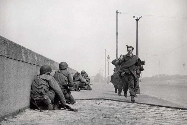 Kapitulierende deutsche Soldaten überqueren die Zeppelinbrücke, während US-Soldaten gedeckt vorrücken. 18. April 1945. Foto: Robert Capa, Copyright International Center of Photography/Magnum Photos