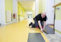 Mike Wanzke, Fachmann der Firma Wohnfühl Konzepte GmbH, verlegt den neuen Fußboden in den Gängen des UKL-Zentrums für Psychische Gesundheit. Foto: Stefan Straube/UKL