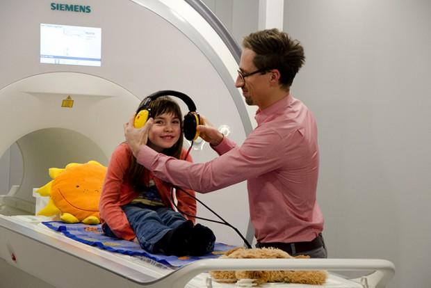 Mithilfe der Attrappe eines Hirnscanners bereitet sich eine junge Probandin auf ein Experiment vor. Foto: MPI CBS