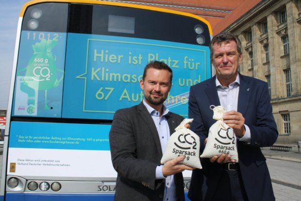 Marc Backhaus und Ronald Juhrs vor dem Bus mit der Klimaschutz-Werbung. Foto: Ralf Julke
