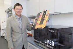 Prof. Eugen Herzau an einer für Forschungszwecke optimierten Digitaldruckmaschine. In der Hand hält er einen digital bedruckten Weinkarton. Foto: Andreas Schröder/HTWK Leipzig