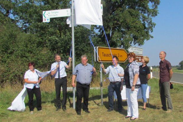Das erste Schild für die neue Elbradwegroute wird an der Fähre von Bergern enthüllt. Foto: Landratsamt Nordsachsen