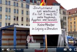 Screenshot Video vom 13. Juli 2016 mit passendem Schild in der Menge. Screenshot Youtube
