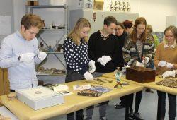 Anfassen ausnahmsweise erlaubt – unter Anleitung von Dozenten kann man am Schnupperwochenende üben, wie ausgewählte historische Objekte richtig gehandhabt und bestimmt werden. Foto: HTWK Leipzig/Museologie