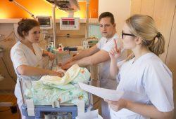 Die beiden Azubis Lisa Köberling (links) und Vivien Plickert kümmern sich gemeinsam mit Pfleger Erik Emrich um einen kleinen Patienten auf der Station E 1.2. Foto: Stefan Straube
