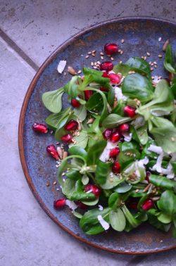 Feldsalat mit Granatapfelkernen, Parmesan und gerösteter Saat. Foto: Maike Klose