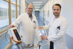 Dr. Boris Jansen-Winkeln (links), leitender Oberarzt in der Viszeralchirurgie, und Dr. Sebastian Krämer, Oberarzt in der Thoraxchirurgie, mit einem Hochdruckinjektor. Er wird genutzt, um unter OP-Bedingungen mit einem definierten Ausgabedruck über eine spezielle Düse den Chemotherapienebel herzustellen. Foto: Stefan Straube / UKL