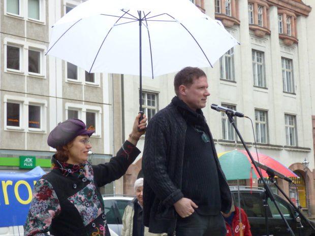 Das Wetter meinte es nicht gut: Initiatorin Barabar Rucha musste Michael Fischer-Art während dessen Ansprache den Regenschirm halten. Foto: Lucas Böhme