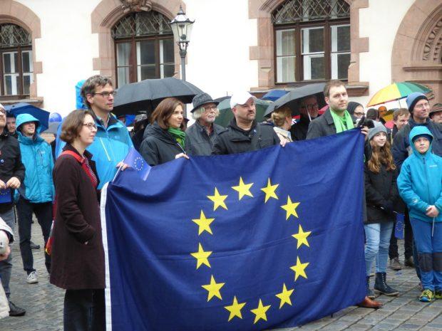 Versammlungsteilnehmer an der EU-Flagge, 3. v.l.: Die grüne Politikerin Katrin Göring-Eckardt. Foto: Lucas Böhme