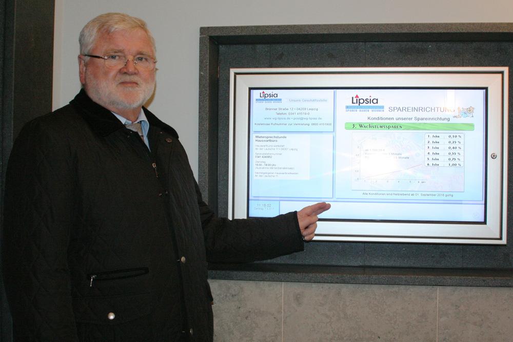 """Lipsia-Vorstand Wilhelm Grewatsch vor einer der neuen elektronischen Haustafeln. Foto: """"Lipsia"""" eG"""