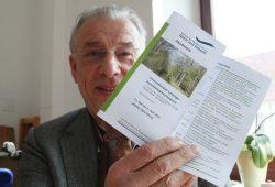 NuKLA-Vorsitzender Wolfgang Stoiber mit dem Flyer fürs Symposium. Foto: Ralf Julke