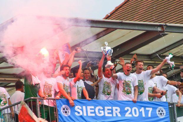 Balkon-Party mit Meisterpokal. Die Spieler der BSG Chemie feiern ihren Aufstieg. Foto: Jan Kaefer