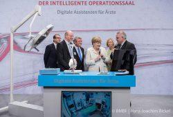 Thomas Neumuth (links) und Andreas Melzer (rechts) vom ICCAS der Universität Leipzig präsentieren der Bundeskanzlerin und weiteren Bundeskabinettsmitgliedern den intelligenten OP-Saal. Foto: Foto: BMBF/ Hans-Joachim Rickel