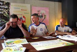 Zuviel Programm? Der Veranstalter Christoph Schumacher (l.) muss nachlesen. Neben ihm Norman Landgraf und Dr. Thomas Feist bei der Pressekonferenz zum 3. Fußballbegegnungsfest 2017. Foto: L-IZ.de
