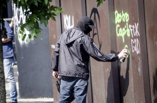 Ein vermummter Demonstrant sprüht bei den Aktionen gegen G20 am Nachmittag des 07.07. etwas an ein Gebäude. Foto: Tim Wagner