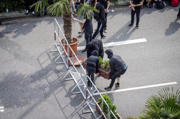 Demonstrierende errichten eine Barrikade an den Landungsbrücken am Nachmittag des 07.07. mithilfe von Palmen und Blumentöpfen der anliegenden Restaurants sowie Absperrgittern der Polizei. Foto: Tim Wagner
