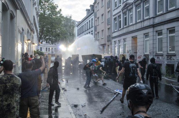 Demonstrierende setzten sich mit Schildern und Brettern gegen den Wasserwerfer zur Wehr bzw. greifen diesen an im Schanzenviertel. Foto: Tim Wagner