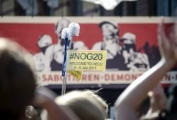 """Klobürsten als Symbol gegen den Ausnahmezustand in Hamburg mit einem Schild #NoG20 vor der Bühne der """"Welcome to Hell"""" Demo. Foto: Tim Wagner"""