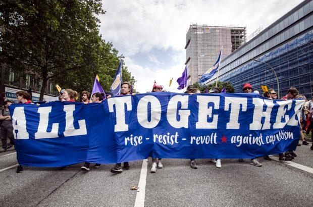 """Block Transparent mit der Aufschrift: """"All Together - rise -resist - revolt - against capitalism"""". Foto: Tim Wagner"""