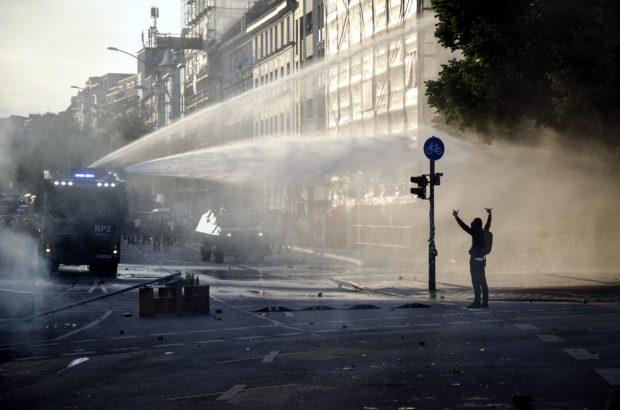 Demonstrant zeigt Wasserwerfer den Mittelfinger am neuen Pferdemarkt. Foto: Tim Wagner