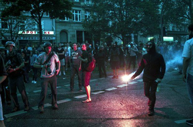 Vermummter rennt mit pyrotechnik, bengalischem feuer, welches rot Leuchtet richtung Schulterblatt. Foto: Tim Wagner