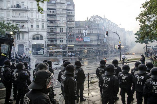 Polizei rückt am Neuen Pferdemarkt Richtung Schulterblatt mit Wasserwerfern vor. Im Hintergrund brennt eine Barrikade und Menschen stehen auf Hausdächern sowie einem Gerüst. Foto: Tim Wagner
