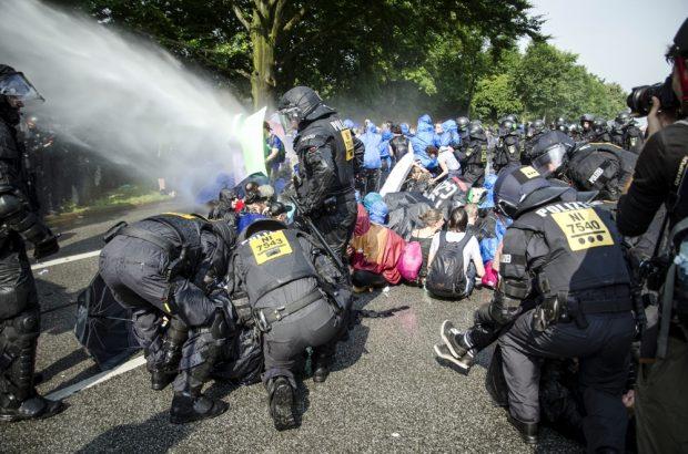 """Die Polizei setzt Wasserwerfer gegen Demonstranten ein, welche die ren die Schröderstiftstraße blockieren. Sie gehören zum grünen und blauen Finger der Aktion: """"Colour the red zone"""" im Protest gegen den G20 Gipfel. Einzelne Personen werden weggetragen. Foto: Tim Wagner"""