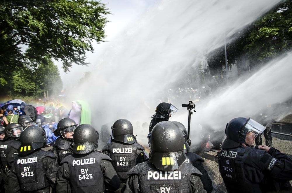 Die Polizei setzt Wasserwerfer gegen Demonstranten ein, welche die Schröderstiftstraße in Hamburg blockieren. Sie gehören zum grünen und blauen Finger der Aktion: