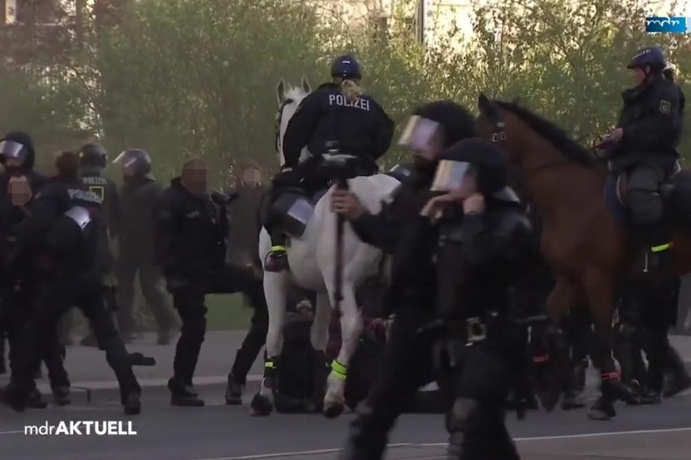 Ein Polizist tritt in eine Personengruppe. Screenshot: MDR
