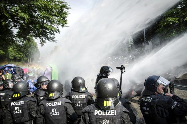 """Weniger spektakulär als brennende Autos, aber eher das Geschehen in Hamburg Die Polizei setzt Wasserwerfer gegen Demonstranten ein, welche die Schröderstiftstraße in Hamburg blockieren. Sie gehören zum grünen und blauen Finger der Aktion: """"Colour the red zone"""" im Protest gegen den G20 Gipfel. Foto Tim Wagner"""
