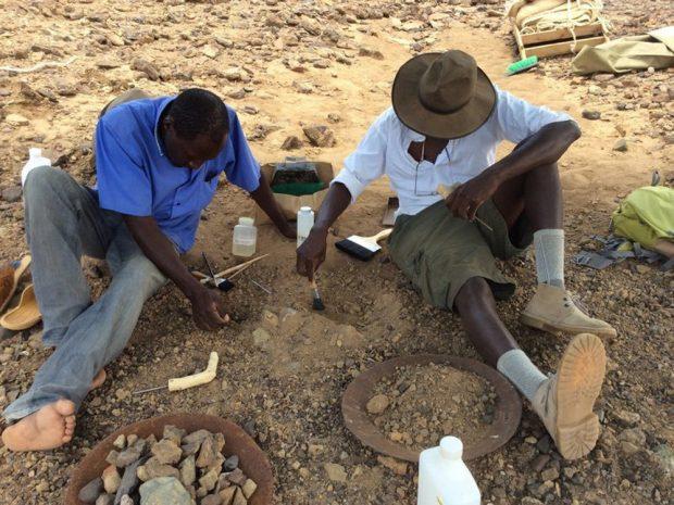 Cyprian Nyete (links) und Isaiah Nengo (rechts) schützen Alesi beim Ausgraben mit Zahnstocher, Pinsel und einem Härter. Foto: Isaiah Nengo