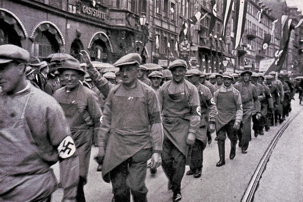 """Der eigentliche Kampf der Parteien dreht sich im Vorfeld der Wahl 1932 vor allem um die Arbeiterklasse. Beliebtes Propagandamittel damals sogenannte """"Cigarettenbilder"""", hier mit dem Untertitel: Deutschland erwacht, aus der Reihe """"Werden, Kampf und Sieg der NSDAP"""" des """"Cigaretten-Bilderdienst"""" in Hamburg-Bahrenfeld. © gemeinfrei"""