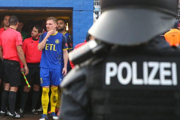Spielunterbrechung. Während die Polizei agierte, warteten die Mannschaften und das Schiedsrichtergespann auf die Fortsetzung der Partie. Foto: Jan Kaefer