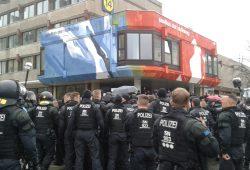 Polizisten drängen Compact-Gegner von der Straße. Foto: René Loch