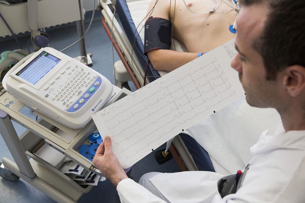 OA Dr. Christian Spies in der CPU am Uniklinikum Leipzig mit einem EKG-Ausdruck. Foto: Stefan Straube/UKL