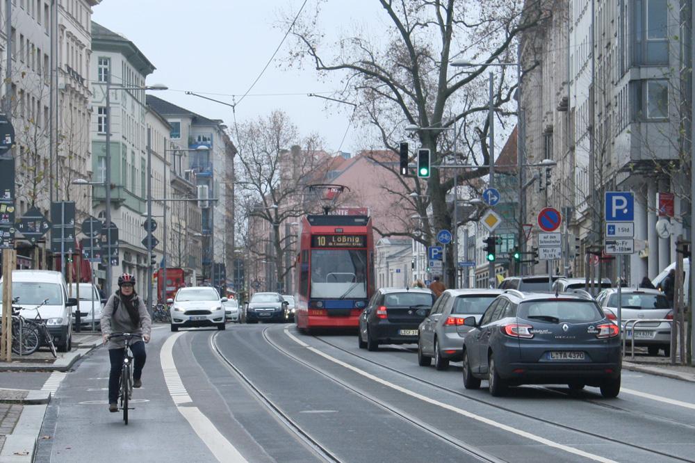 Karl-Liebknecht-Straße mit Radfahrern, Pkw und Straßenbahn. Foto: Ralf Julke