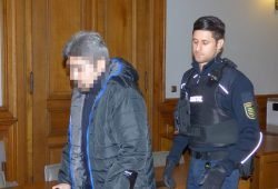 Ein Justizbeamter führt den Angeklagten Ghulam R. (39), der nach seinem Suizidversuch an Krücken geht, zur Anklagebank. Foto: Lucas Böhme