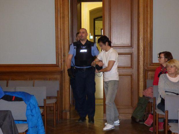 Ein Justizbeamter bringt Dovchin D. (39) in Handfesseln in den Saal. Foto: Lucas Böhme