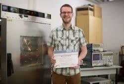 """Florian Strakosch im """"Smart Diagnostics""""-Labor der HTWK Leipzig. In der Klimakammer (links) wurde das Getriebe simuliert, die Messtechnik (rechts im Bild) erzeugte und wertete die Funksignale aus. Foto: Robert Weinhold/HTWK Leipzig"""